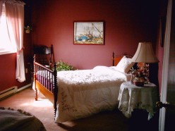 the burgundy bedroom has a comfortable old fashioned double spool bed